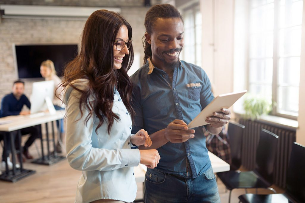 man and woman looking at tablet in office