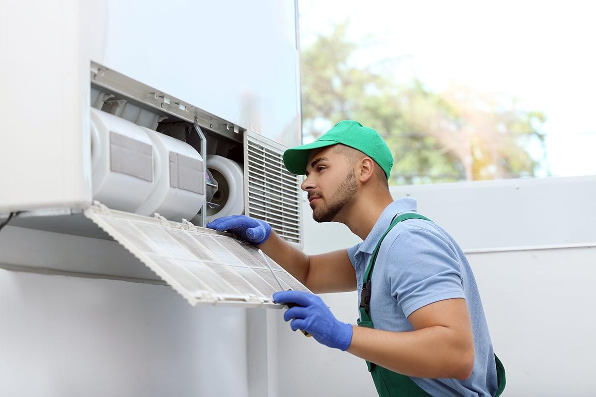 HVAC technician examining unit