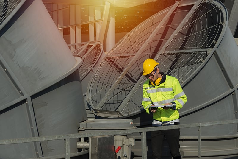 Commercial refrigeration technician performing maintenance on cooling tower