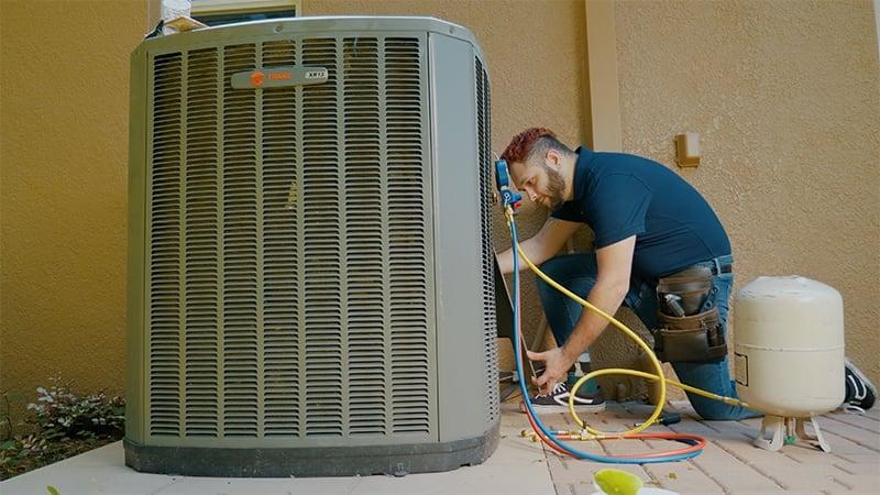 Residential HVAC technician working on HVAC unit