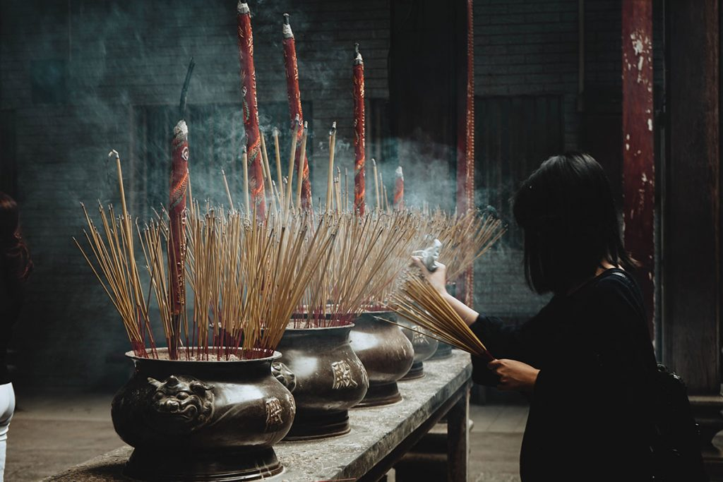 woman putting incense sticks on pot in vietnam